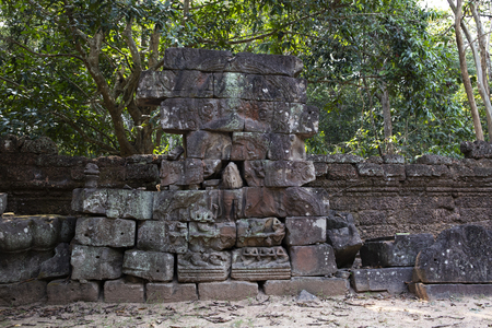 Ancient ruins of Krol Ko temple in Angkor Wat complex, Cambodia. Stone bas-relief restoration. Stone temple ruin. Abandoned temple in green jungle. Tourism and sightseeing place in Asia.