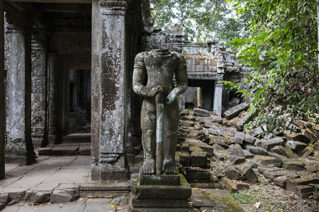 Ancient ruins of Preah Khan temple in Angkor Wat complex, Cambodia. Headless statue of demolished palace. Stone temple ruin. Abandoned temple in green jungle. Tourism and sightseeing place in Asia. Фото со стока