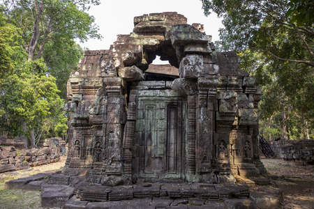 Ancient ruins of Krol Ko temple in Angkor Wat complex, Cambodia. Small shrine with stone bas-relief. Stone temple ruin. Abandoned temple in green jungle. Tourism and sightseeing place in Asia. Фото со стока