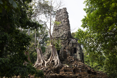Ancient ruins of Preah Palilay temple in Angkor Wat complex, Cambodia. Demolished hindu temple with trees. Stone temple ruin. Abandoned temple in green jungle. Tourism and sightseeing place in Asia.
