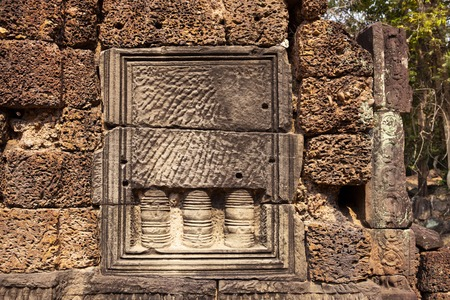 Ancient hindu temple decor, Angkor Wat, Cambodia. Banteay Thom ruin. Khmer architecture heritage landmark detail. False window in weathered sand stone masonry. Abandoned temple wall in tropical jungle Фото со стока