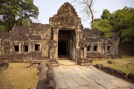Ancient ruins of Preah Khan temple in Angkor Wat, Cambodia. Decorated entrance with stone bas-relief. Stone temple ruin. Abandoned temple in green jungle. Tourism and sightseeing place in Asia. Фото со стока