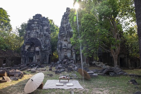 Ancient ruins of Banteay Thom temple in Angkor Wat complex, Cambodia. Japanese styled picnic near abandoned place. Khmer heritage temple in green jungle. Tourism and sightseeing place in Asia. Фото со стока