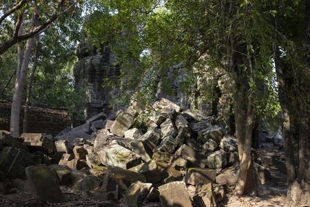 Ancient ruins of Krol Ko temple in Angkor Wat complex, Cambodia. Demolished stone pile in tropical forest. Stone temple ruin. Abandoned temple in green jungle. Tourism and sightseeing place in Asia. Фото со стока - 105784290