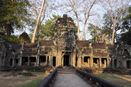 Ancient ruins of Ta Prohm temple in Angkor Wat complex, Cambodia. Decorated entrance with stone bas-relief. Stone temple ruin. Abandoned temple in green jungle. Tourism and sightseeing place in Asia.