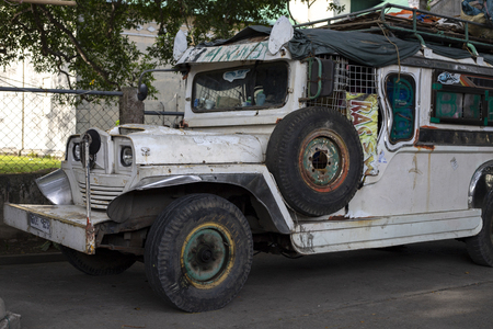 Dumaguete, the Philippines - 27 July 2018: White vintage jeep on street. Street scene in Philippines. Traditional symbolic military car. Vintage jeep car. Filipino iconic public transport. Old jeepney Editorial