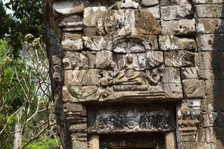 Ancient ruins of Preah Palilay temple in Angkor Wat complex, Cambodia. Stone bas-relief closeup. Stone temple ruin. Abandoned temple in green jungle. Tourism and sightseeing place in Asia.