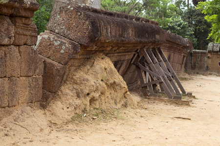 Wall ruin of ancient building with wooden scaffolding. Ancient temple masonry restoration. Old sandstone wall in angkorian temple. Cambodian place of interest. Archaeological site. Asia travel photo