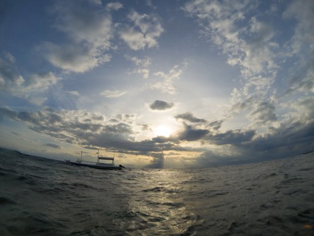 Sea and cloudy sunset fish eye photo. Tropical sunset on sea. Tropic island seashore with sun and cloud. Sea and sky double landscape. Sunset seascape with traditional wooden boat. Philippine vacation