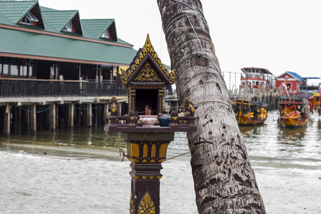 Small buddhist shrine on seaside of Koh Rong island, Cambodia. Traditional religion of khmer people. Outdoor buddhist shrine. Little temple on pillar. Seaside view with wooden boat. Fishermen belief