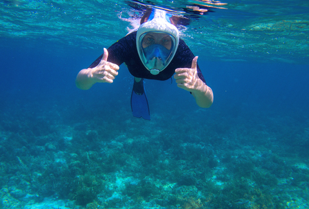 Woman underwater shows thumb up. Snorkel in coral reef of tropical sea. Young girl in full-face snorkeling mask. Underwater photo of oceanic landscape. Active seaside vacation. Seaside activity 版權商用圖片