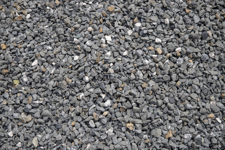 Grey gravel closeup photo for background. Sharp gray stones for construction. Gravel texture. Road or building construction supply. Grey stones bunch for wallpaper or banner template. Natural texture