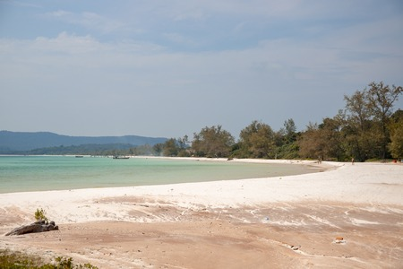 Tropical shore with turquoise blue water and white sand beach. Peaceful landscape of exotic paradise. Exotic bounty beach with sea tide and white sand. Cambodian island Koh Rong tourist photo