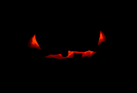 Halloween pumpkin scary face with candle inside, concept photo on black background. Pumpkin face glowing silhouette. Halloween party decor. Carved pumpkin with scary face and red glow in darkness