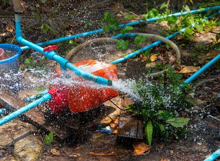 Breakthrough water pipe. Broken water supply. Fresh water recourse waste. South Asia water supply problem. Blue pipes and orange tank mechanism. Splash from pipeline. Broken plumbing in summer garden