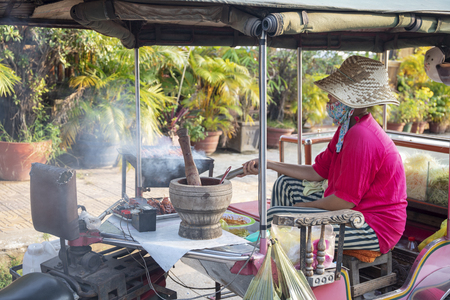 Kampot, Cambodia - 12 April 2018: khmer woman cooking meat kebab on street kitchen. Cambodian streetfood eatery. Mobile kitchen and woman cooker. Simple job and private business in South Asia