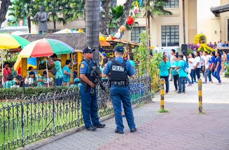14 Nov 2018 - Cebu, the Philippines: two policemen protect the local festival. Ethnic people policemen. Filipino festival safety. Big city outdoor event. Harvest festival in park. Philippine fiesta