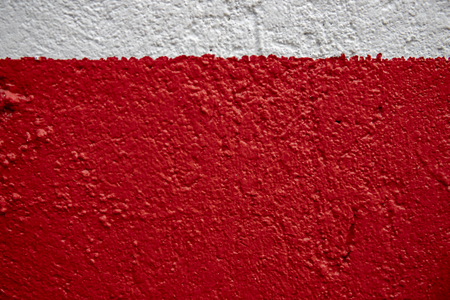 White and red painted wall photo. Painted brushed texture. Grungy concrete wall closeup. Rustic architecture background. Concrete house wall. Rough painted surface. Vintage or shabby chic backdrop
