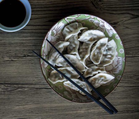 Dumplings in plate on wooden background. Chinese cuisine dish top view photo. Meat dumplings pile in ceramic bowl with sticks. Traditional asian dish menu. Rustic simple food for lunch or dinner