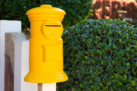 Yellow post box in green garden. Decorative postbox closeup photo. Vintage mail box and green hedge. Colorful garden in traditional english style. Summer outdoor landscape with mailbox