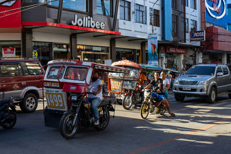 Dumaguete, the Philippines - 10 Mar 2019: Motorbike on asian city street. Filipino tricycle and bike. Jollibee cafe. Street traffic in Asia. Modern city transport. Urban people lifestyle outdoor scene