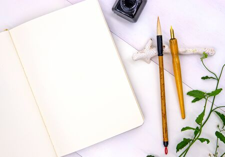 Blank page of sketchbook with calligraphy tools and green foliage. Notebook top view photo on white background. Oriental flat lay with empty page. White paper notepad mockup for message or logo design