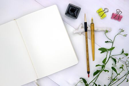 Blank page of sketchbook with calligraphy tool. Notebook top view photo on white background. Spring or summer flat lay with empty page. White paper notepad mockup for sketching or drawing. Artist desk