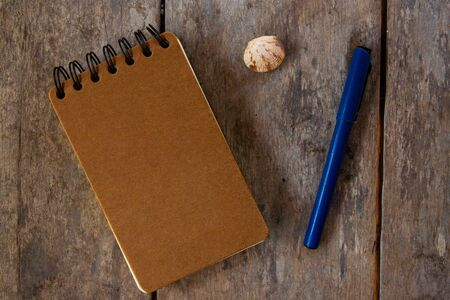 Spiral notepad craft cover and pen on wooden background. Empty sketchbook top view photo. Brown paper notepad and writing tool on rustic table with shell. Travel book mockup. Craft stationery design Stock Photo