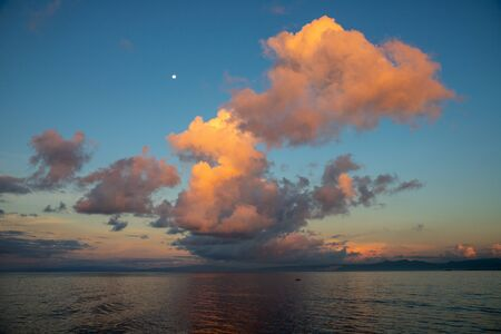 Morning dew sky with orange cloud and moon. Seaside sunrise photo with moon and clouds. Orange sunset or sunrise in tropical seaside. Summer travel. Exotic island hopping cruise or ferry