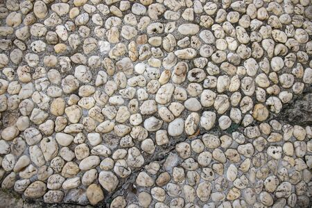 Grungy photo texture of pebble paving. Tiny marble gravel road. Pebble texture. Marine or seaside construction material. Stone mosaic natural backdrop. White pebble top view. Small stone flat surface