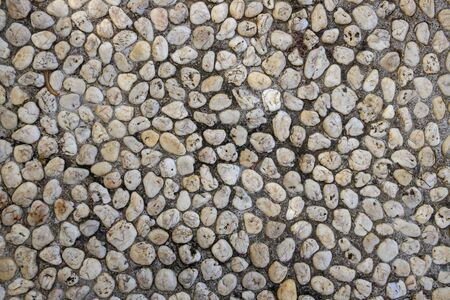 Abstract photo texture of pebble paving, top view background. White pebbles in grey sand top view. Rounded marble paving. Natural backdrop of marine style outdoor floor. White marble stone surface