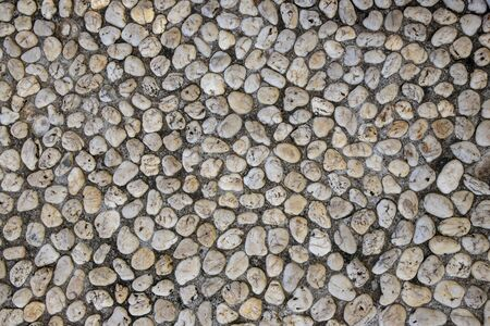 Natural photo texture of tiny pebble, top view background. White pebbles in grey sand top view. Rounded marble paving. Abstract backdrop of marine style outdoor floor. White marble stone surface