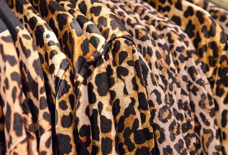 Leopard clothes on hangs in a fashion shop. Stylish animal print on top garment. Fashion shop Black Friday sale. Clothes department store. Textile retailer with popular brand. Bright streetwear