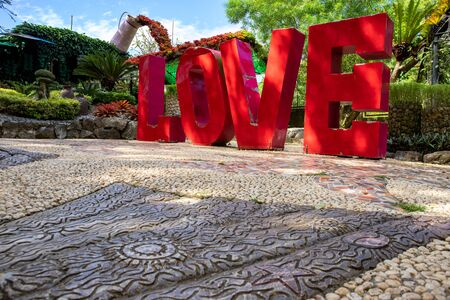 Love red letters in green tropical park, outdoor decor photo. Huge letters of Love inscription. Selfie or photo spot idea. Public park attraction. Love standing letters for wedding photography
