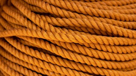 Yellow cord background, close-up photo. Braided rope texture. Ship or rock climbing tackle. Natural material woven cordage. Simple rope bulk concept. Alpine mountaineering equipment. Safety orang rope Stok Fotoğraf