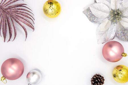 Christmas greeting flat lay with text space and fir tree decor. New Year composition on white background. Winter holiday banner template. Pink and golden firtree bauble on table top view