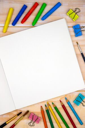 Blank page of open sketchbook with art tools on wooden table. Artistic table top view photo. Drawing or sketch mockup on square notebook page. Blank paper for painting. Crayon and pencil for kids art