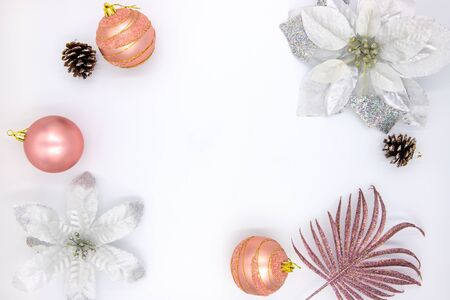Christmas flat lay with text space and fir tree decor. New Year composition on white background. Winter holiday banner template. Pink and golden firtree bauble, pine and poinsettia on table top view