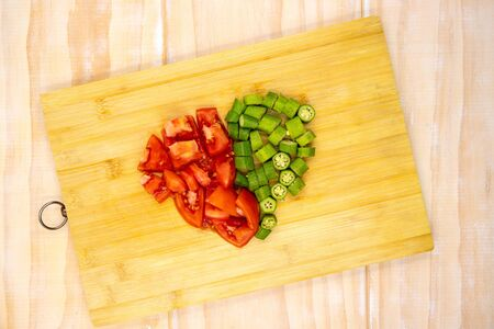 Tomato and okra vegetables cut on cutting board. Healthy vegetarian salad preparation. Green and red vegetable on cutboard top view photo. Rustic lifestyle kitchen. Healthy summer food. Raw eating