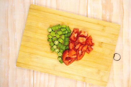 Tomato and okra vegetables cut on cutting board. Healthy vegetarian salad preparation. Vegetables on cutboard top view photo. Rustic lifestyle kitchen. Healthy summer food. Summertime diet. Raw eating