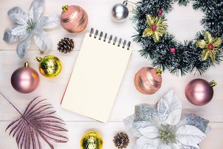 Christmas tree decor and spiral notebook on wooden table. Winter holiday message photo mockup. Christmas sketchbook flat lay. New Year greeting card or banner template. Pink and gold fir tree bauble