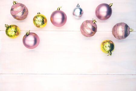 Christmas tree ball composition on wooden table. Winter holiday header photo backdrop. Christmas flat lay with place for text. New Year greeting card or banner template. Pink and gold fir tree bauble