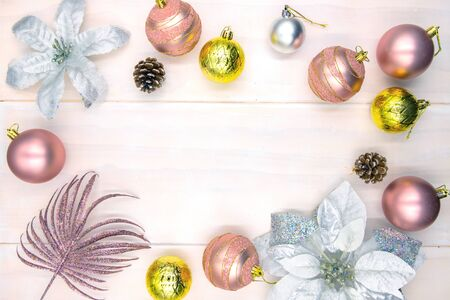 Christmas tree ball and poinsettia decor on wooden table. Winter holiday backdrop. Merry Christmas flat lay with place for text. New Year greeting card or banner template. Pink gold fir tree bauble