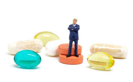 Businessman and pills on white background. Miniature figurine of business man macro photo. Pharmacy corporation and heathcare industry. Drug production profit. Pharma business concept. Medical control