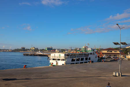 Dumaguete, the Philippines - 10 Mar 2020: sea port and passenger ferry. Maritime delivery of cargo and passenger. Sunny morning landscape with port, passenger ferry boat, and modern city