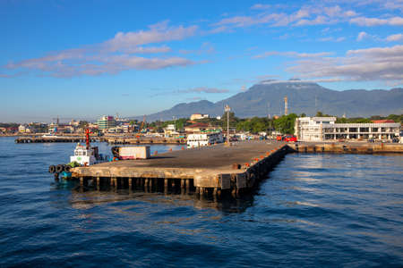 Dumaguete, the Philippines - 10 Mar 2020: empty port pier of small town. Tropical island hopping cruise. Maritime delivery of cargo and passenger. Sunny morning landscape with port, city and mountain Redakční