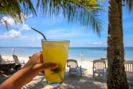 Woman hand with fresh juice on tropical beach landscape. Tropical island vacation on luxury resort. White sand beach with chairs. Sunny day healthy refreshing drink. Lime or orange juice in glass