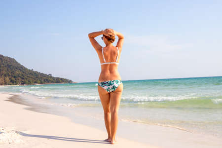 Young woman on white beach. Tanned tourist on empty tropical beach.