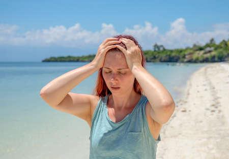 Sunstroke on beach, woman with headache on vacation. Bright sun negative impact.