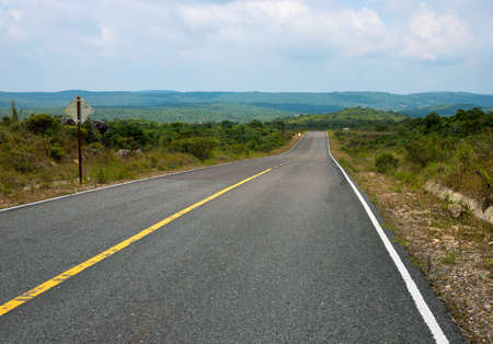 Beautiful road without transport. Empty highway in summer landscape. Asphalt road with green roadside. Abandoned landscape with road and sign. Car or motorbike travel in Asia. Transportation concept Stockfoto